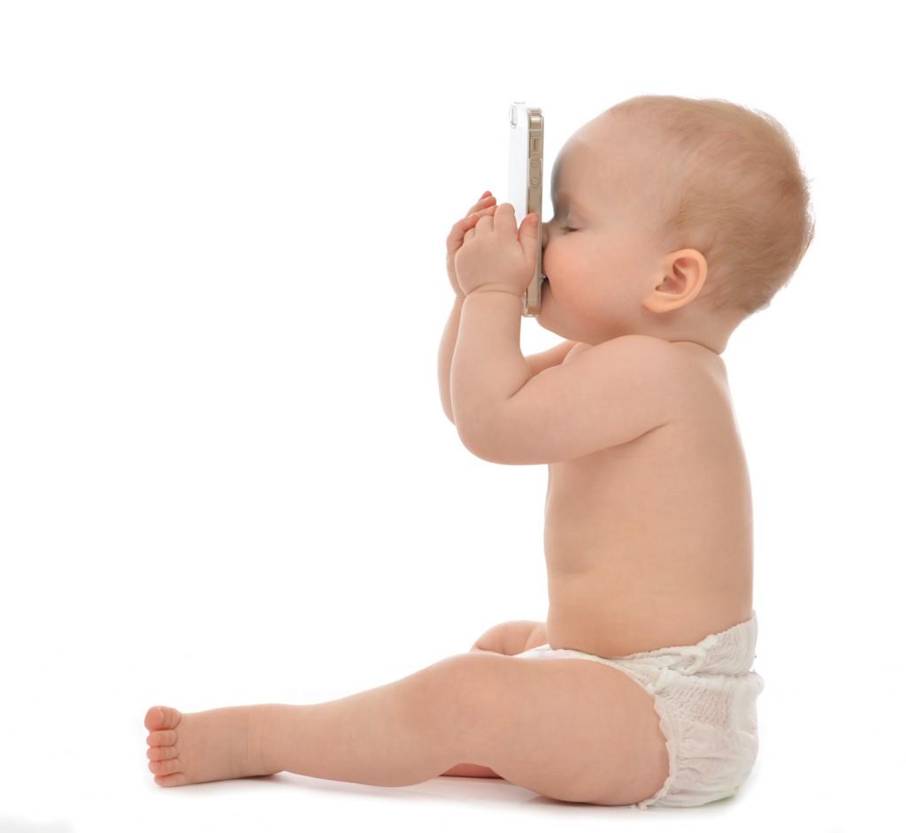 un enfant heureux embrasse le téléphone portable. Danger des portable pour la santé.