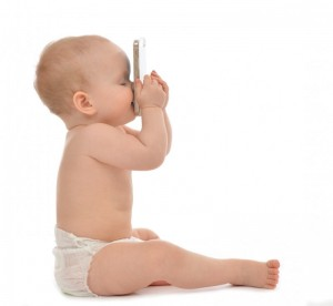 Happy child baby toddler sitting smiling kissing mobile cellphone on a white background
